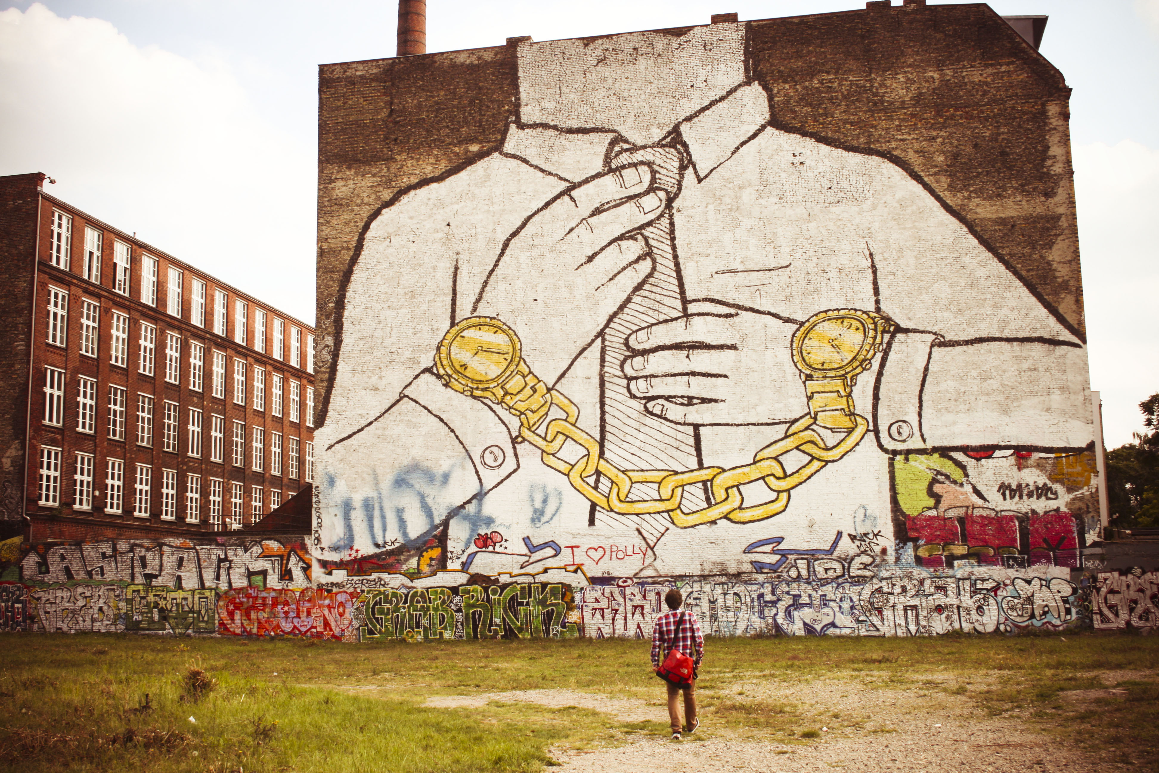 A photo of a mural on the side of a building. The mural depicts a person in a white shirt from the neck down the waist; their hands are in gold handcuffs.