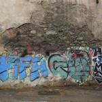 "A homeless man walks past graffiti that reads ""FIFA go home"" in Rio de Janeiro"