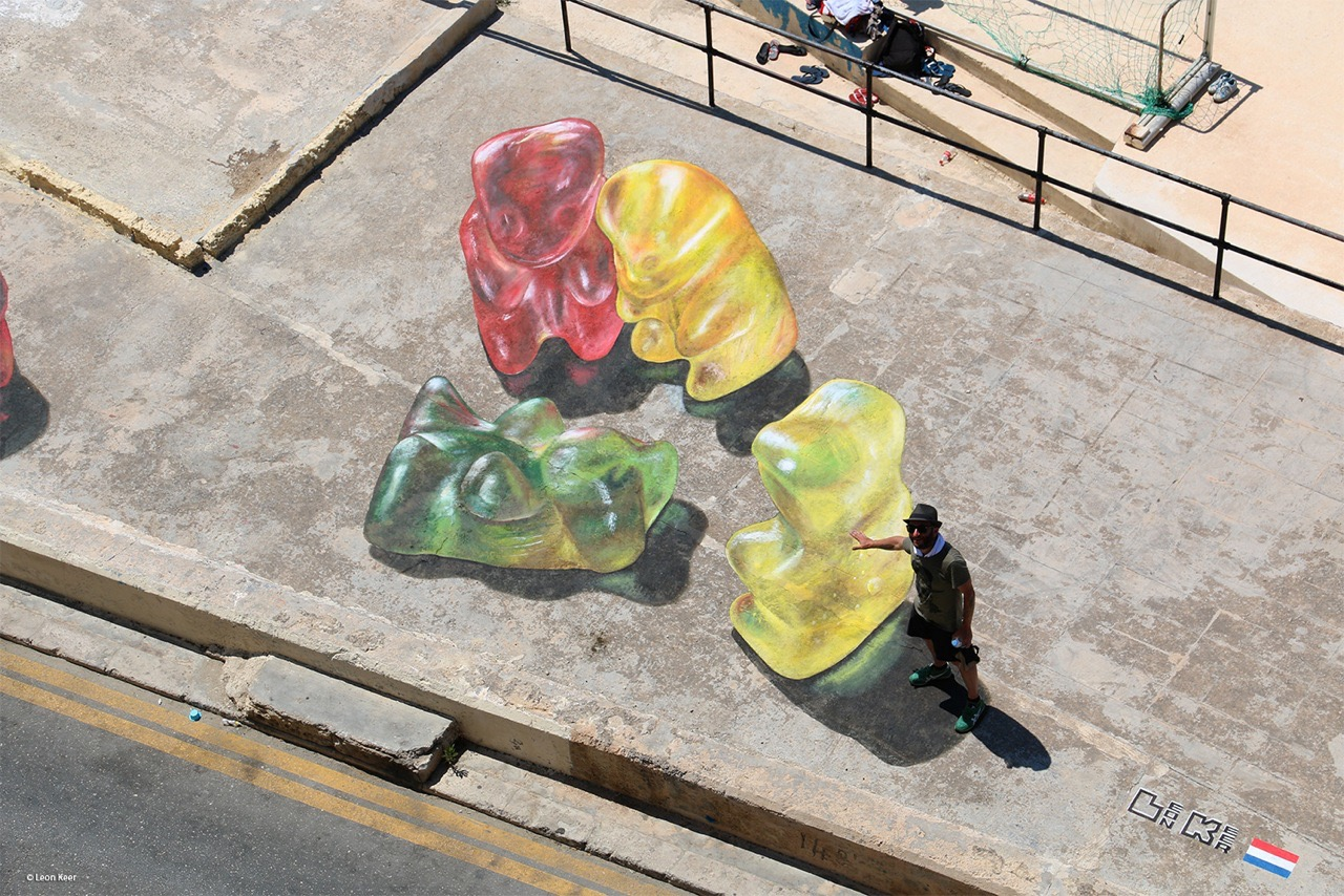 3d street art by Leon Keer at Malta Streetart Festival. Gummy bears gather around 3