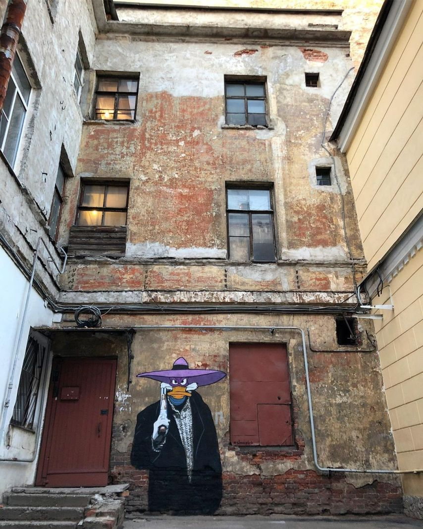 Avenger in Black Street Art in Saint Petersburg, Russia by Slava Ptrk futuring russian movie Brat, brother, and disney darkwing duck 1