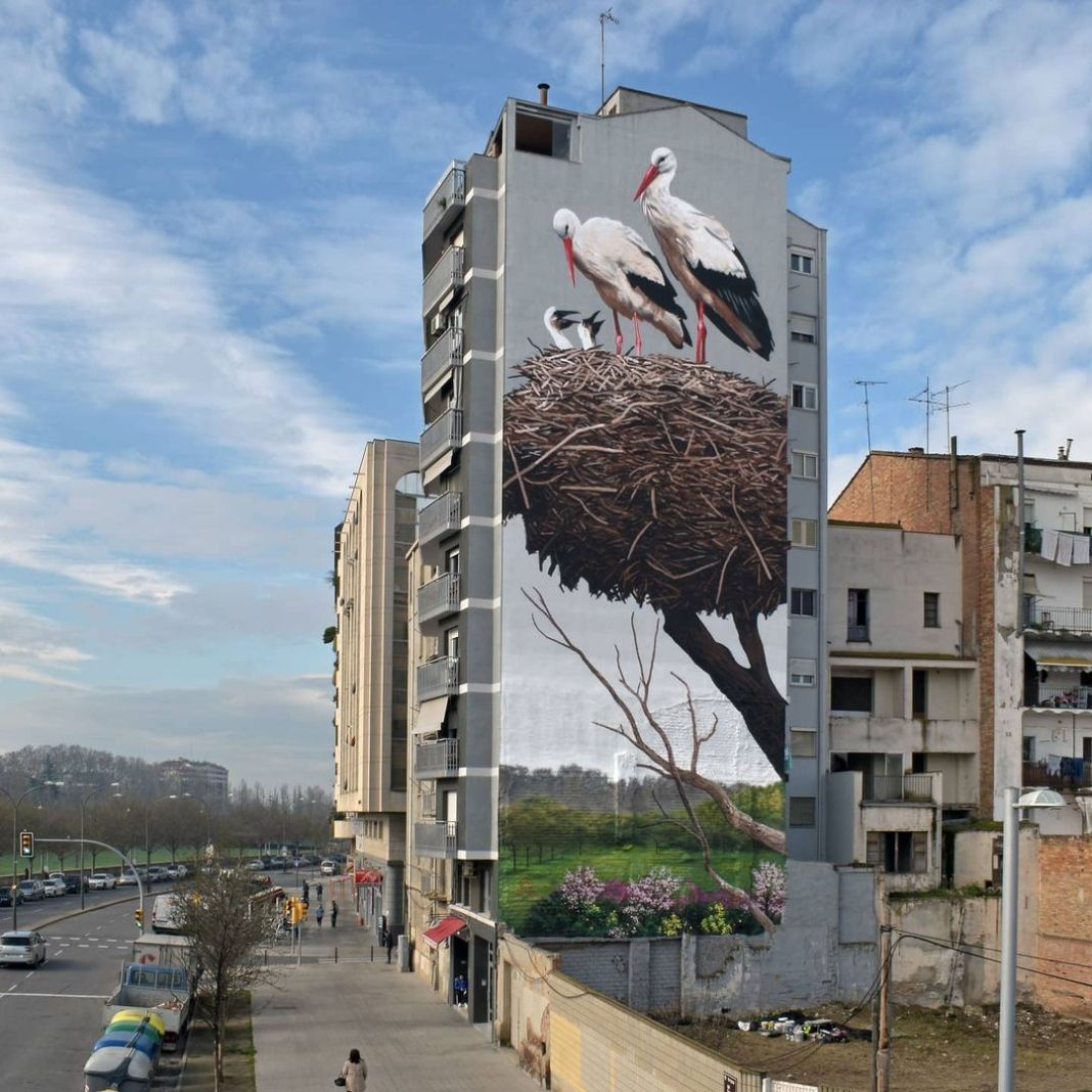 Street Art Mural of a stork nest by street artist, muralist and painter Oriol Arumí in Lleida, Spain